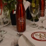 A photo of a 50th anniversary water bottle and an array of glasses and plates on a table