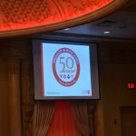 A projector screen with a 50th anniversary slideshow
