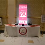 A table with 50th anniversary banner and signs