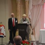 A man and a woman speaking behind a lectern