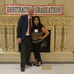 A man and a woman smiling for the camera with destination graduation banner on the wall